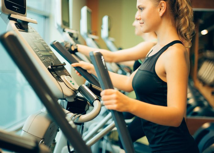 Woman at the gym using elliptical machine for cardio training