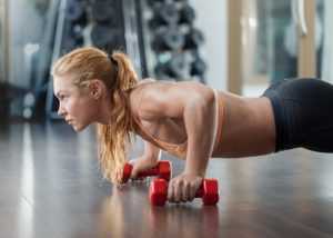 Woman using dumbbells to do pushups for strength training