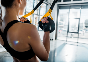 Woman doing TRX strength training at the gym