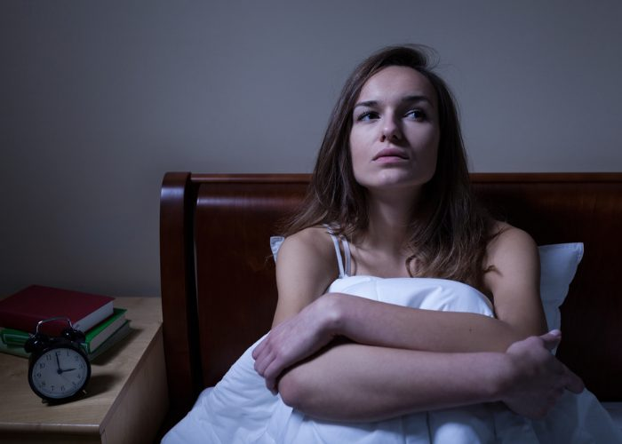 Woman with insomnia sat up in bed at night