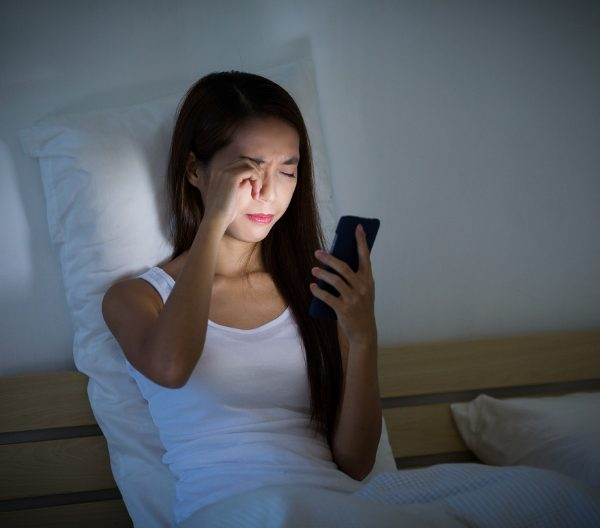 Woman rubbing her eyes while staring at her phone in bed at night and with glaring blue light