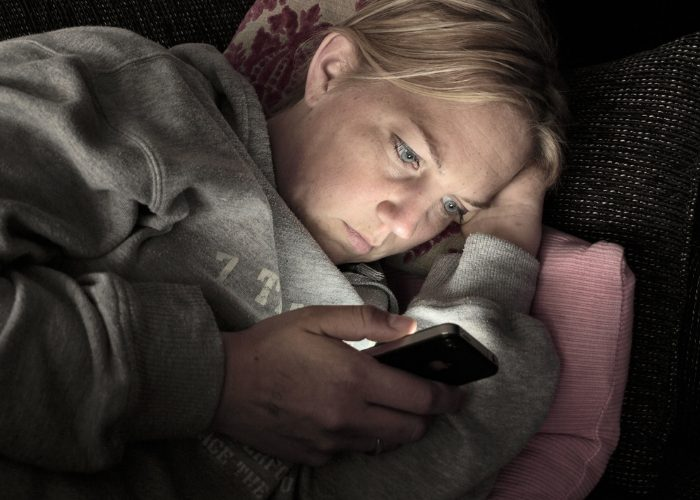 Woman in a hoodie jumper laying on her side on a couch in the dark and staring at her smartphone with glaring blue light