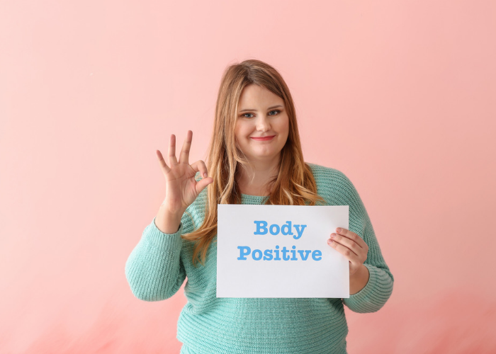 Plus size woman holding up a body positive sign and making the OK sign with her hand