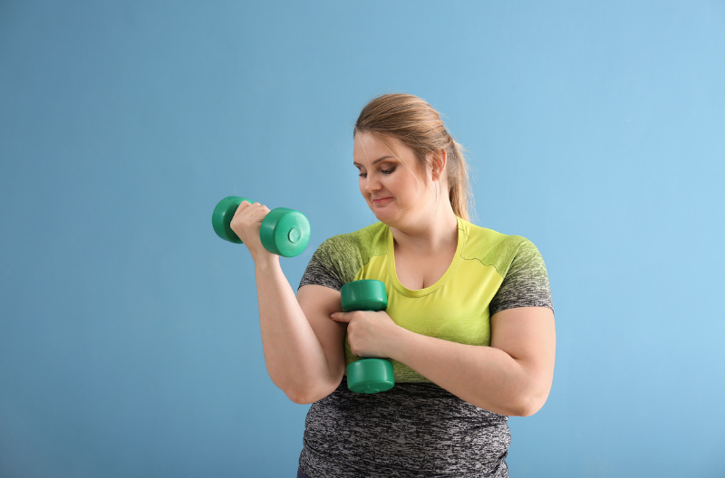 Plus size woman in exercise gear doing dumbbell curls and body positive workout