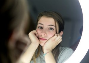 Teenage girl looking sad in a beauty mirror after being fat shamed