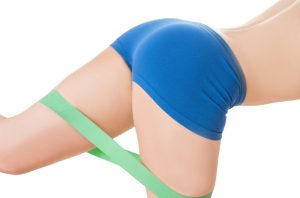 Close up on a woman wearing tight blue shorts working out with a booty band around her thighs