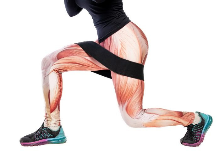 Woman in muscle pattern leggings doing a lunge and lift exercise with booty band around her thighs