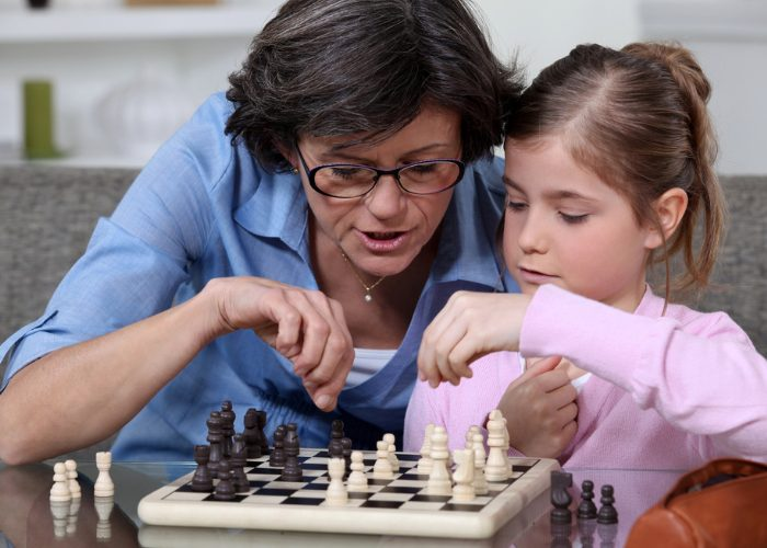 Mother teaching her daughter how to play chess for brain training