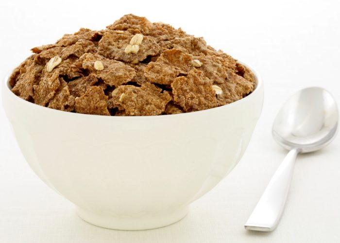 Bowl of wheat bran cereal in a white bowl and a spoon next to it