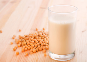 A glass of non-dairy soy milk on a wooden table with a pile of soy beans next to it