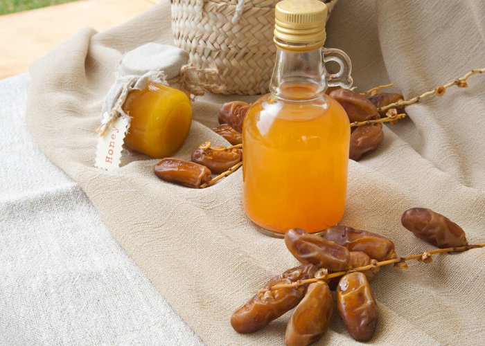Bottle of date vinegar on a brown cloth with fresh dates around it