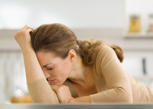 Depressed woman laying on the kitchen counter with her head in her hands
