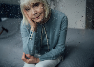 Depressed elderly woman staring through a glass window with raindrops on it