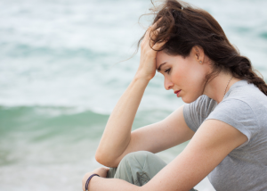 Sad woman by the beach holding her head in her hands