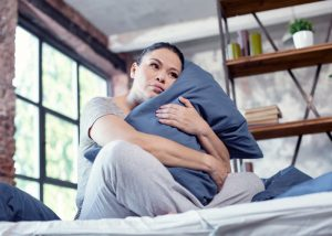 Depressed woman holding onto her pillow in bed