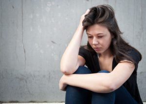 Young, depressed woman sitting with her back against the wall