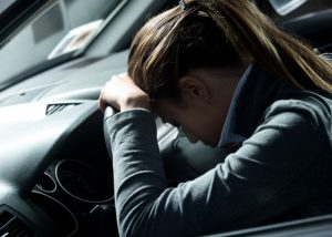 Tired and depressed woman in a formal work jacket laying her head on the dashboard of her car