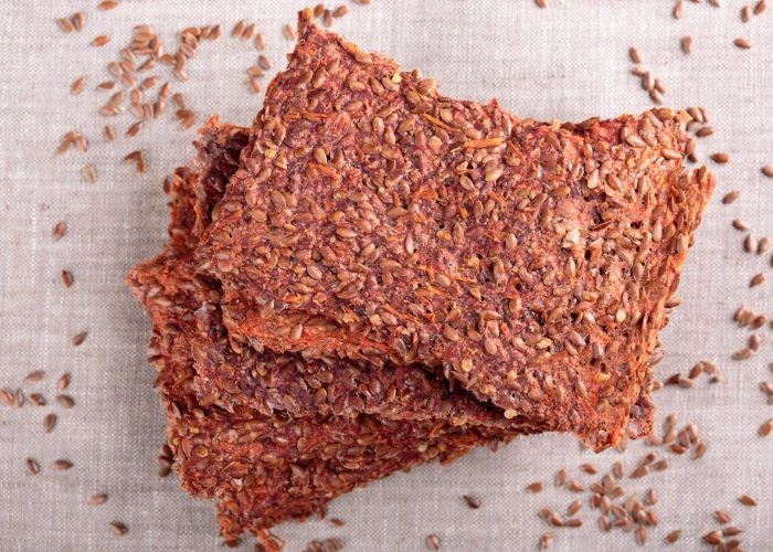 Pieces of stacked healthy fiber crispbreads with seeds sprinkled around it