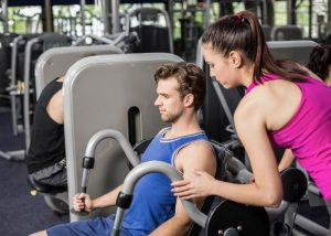 Personal trainer coaching a male client at the gym