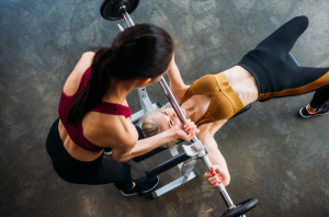 Female personal trainer coaching another lady doing weights on the bench