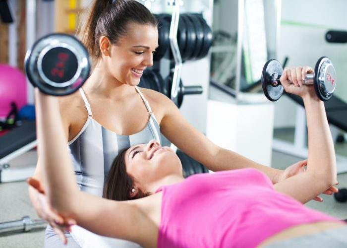 Female personal trainer coaching a woman training with dumbbells at the gym
