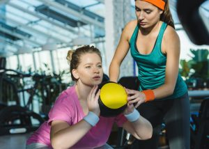 A female personal trainer coaching her female trainee through a workout at the gym