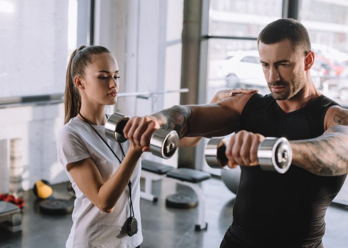 Female personal trainer coaching a male client at the gym using weights