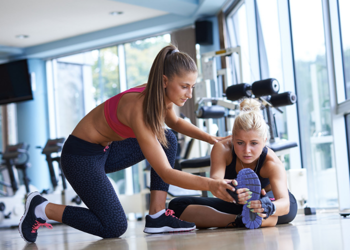 Personal trainer coaching a young woman on proper stretching techniques at the gym