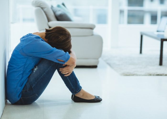 Depressed woman sitting on her living room floor with her head on her knees