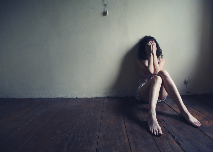 Depressed woman sitting on the floor in a dark room with her back against the wall