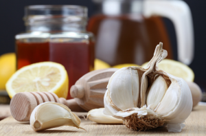 natural antibiotics such as honey, and cloves of garlic on a wooden table