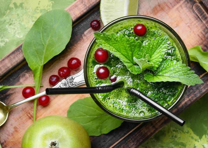 Top down view of a glass of spinach and cranberry smoothie topped with mint leaves and whole cranberries