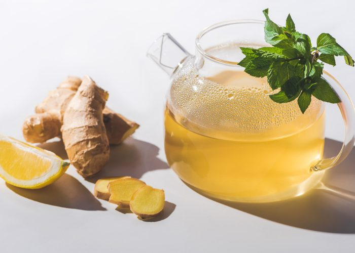 Clear glass teapot with ginger and mint tea, and fresh ginger and a lemon wedge beside it