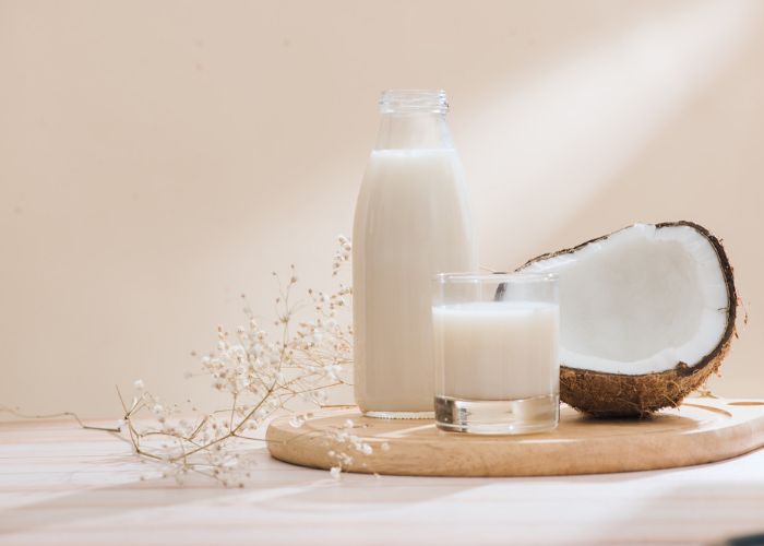 A bottle of coconut milk, a glass of coconut milk and half an open coconut set on a round wooden board, presented with delicate white flowers against a pale background