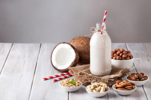 a bottle of non-dairy milk with a straw in it, surrounded by non-dairy milk sources like fresh coconuts, nuts, and grains