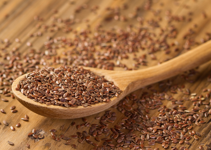 A wooden spoon full of flax seeds