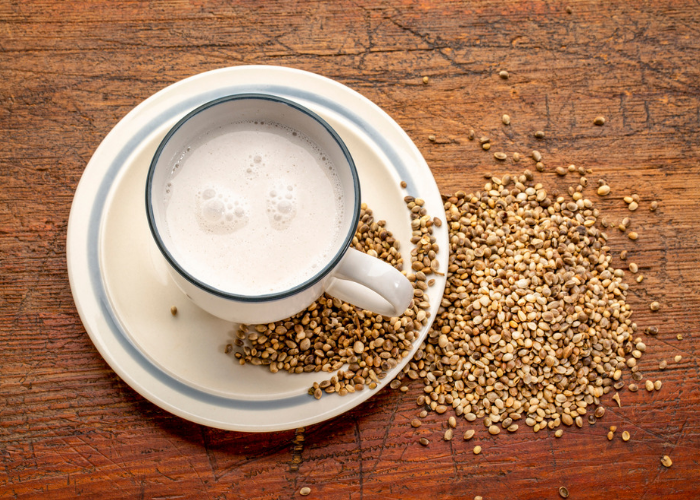 A cup of non-dairy hemp milk on a saucer with hemp seeds scattered next to it