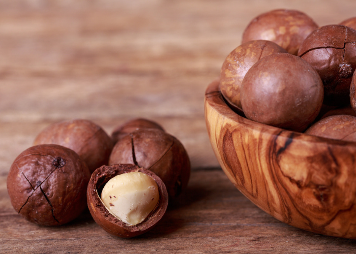Close up of macadamia nuts on a wooden table, and half a wooden bowl full of macadamia nuts