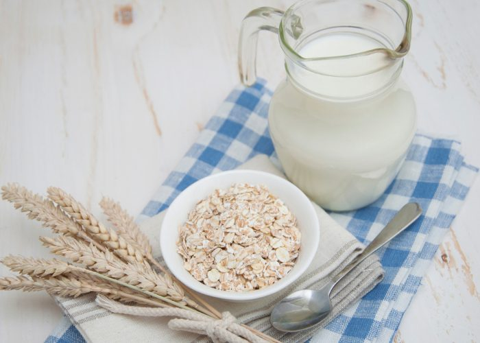 A jug of non-dairy oat milk, a small bowl of fresh oats and a spoon on a blue checkered tablecloth