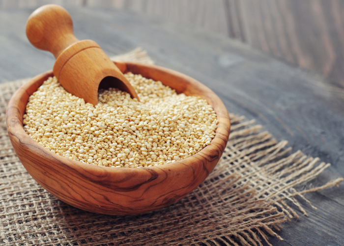 Wooden bowl with a scoop filled with quinoa