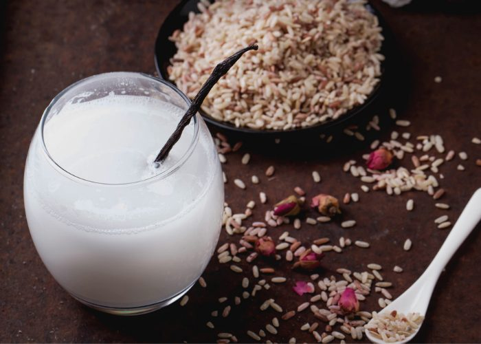 A glass of non-dairy rice milk with a straw, and rice scattered around it