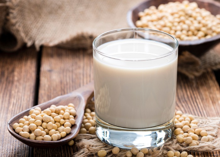 A glass of non-dairy soy milk with a wooden spoonful of soybeans next to it on a wooden table