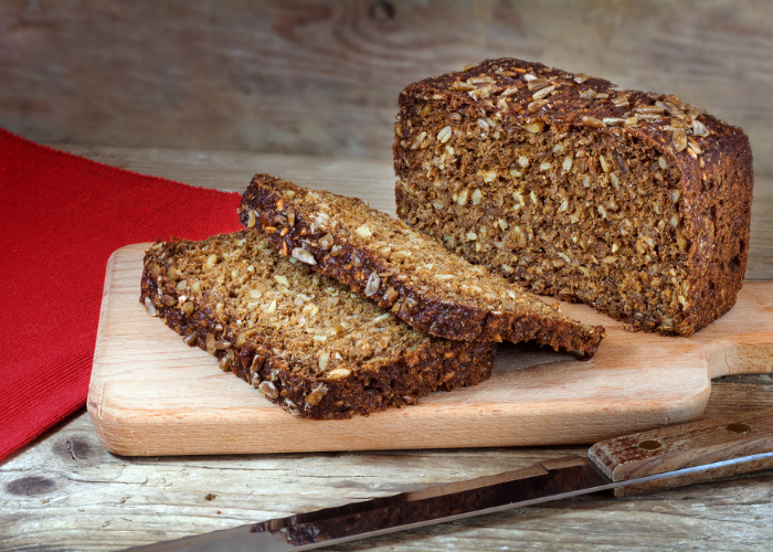 Loaf of protein bread with whole grains and seeds sliced on a wooden board with a red tablecloth in the corner