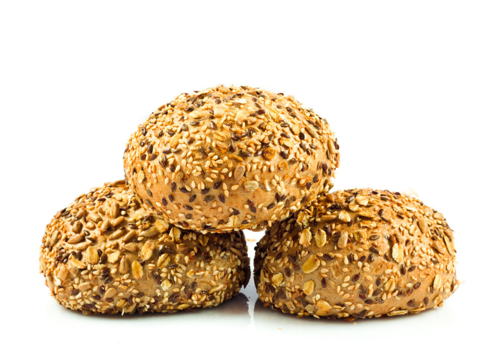 Round protein bread buns with seeds and grains on a white surface and white background