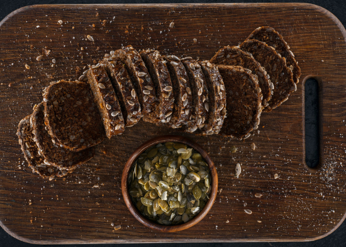 Sliced loaf of dark protein bread with a small bowl of pumpkin seeds on a dark wooden board