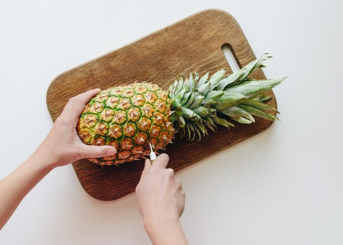 Woman cutting a whole pineapple on a wooden chopping board