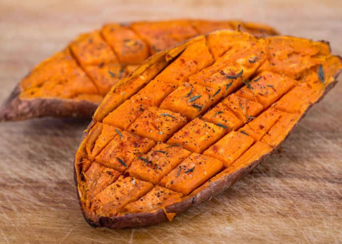 Two halves of a sweet baked potato laid on a wooden board