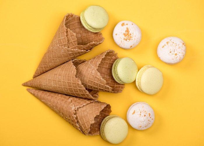 Empty ice cream wafer cones and light colored macaroons laid against a yellow background