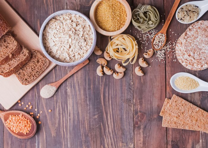 Top down image of different carbohydrate foods on a wooden table