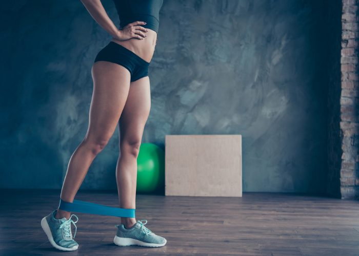 Woman with fit body working out with booty band around her ankles